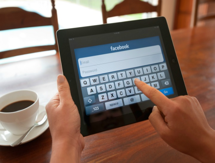 Woman logging into Facebook using digital keypad. Close-up shot of her hands and the iPad screen. She is touching the screen. This shot shows the ipad being used in a casual environment.