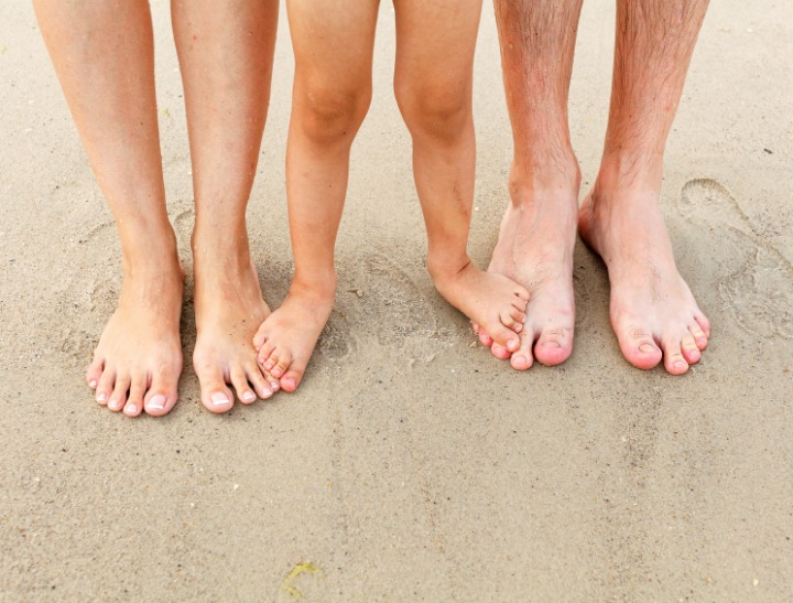 Family feet in the sand on the beach