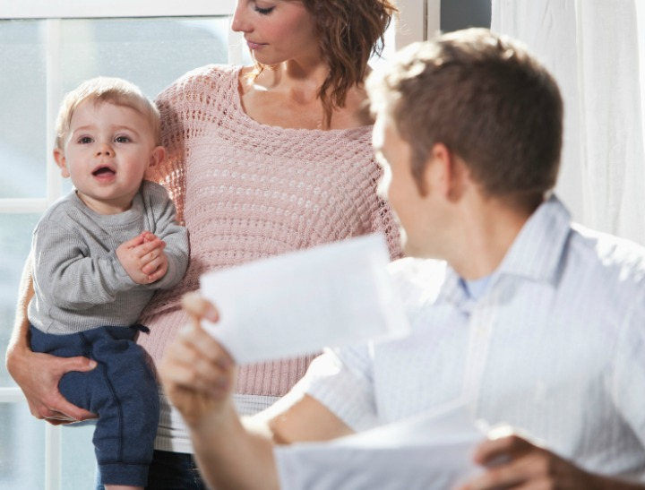 Young family at home.  Mother (20s) holding baby (8 months).  Father out of focus, paying bills in foreground.