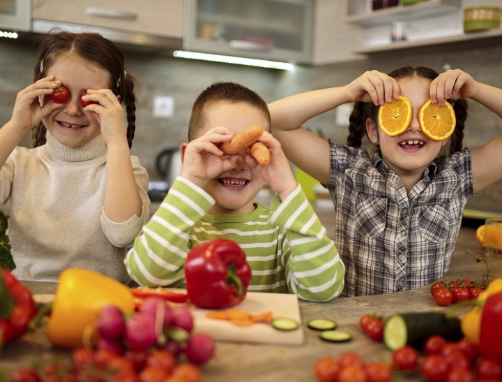 Three little children holding slices of fruit and vegetables over their eyes and having fun in the kitchen.