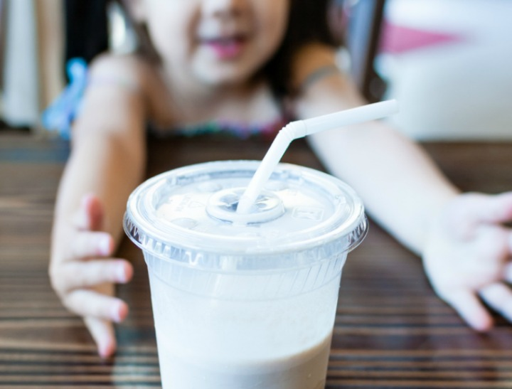 Little girl shares her milk while sitting at coffee shop.