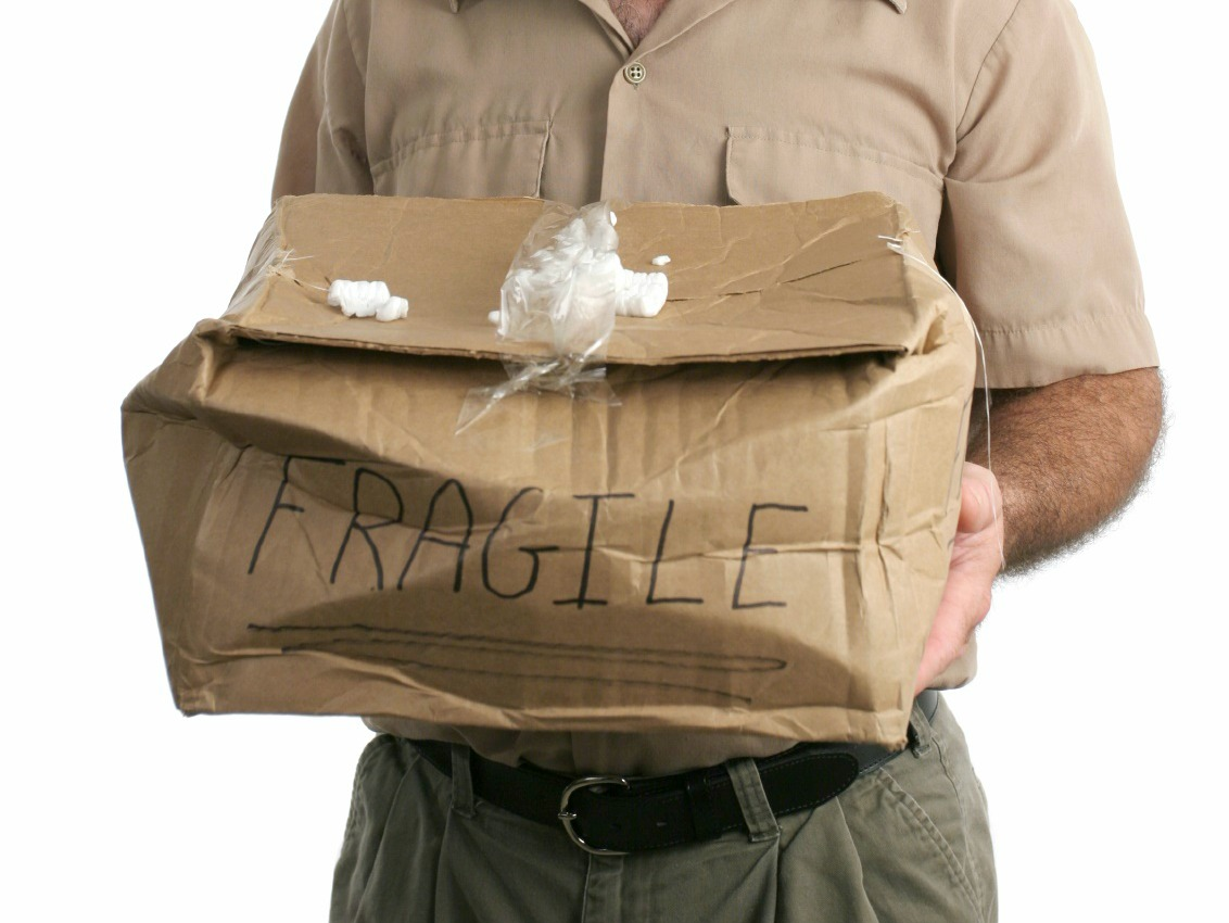 A delivery man holding out a smashed package and looking very sorry.  Isolated.
