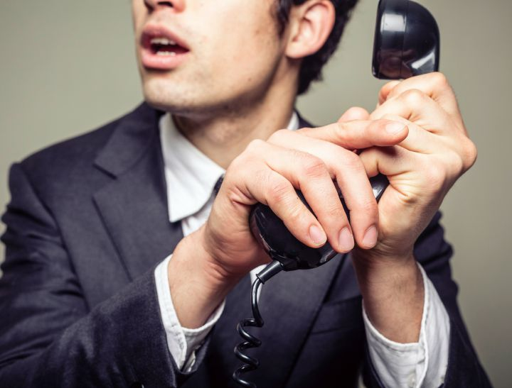 Businessman is covering the phone to speak in private to someone in the room