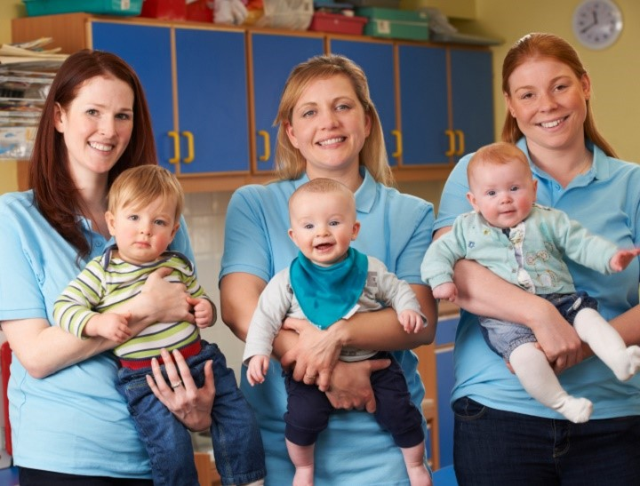Group Of Workers With Babies In Nursery