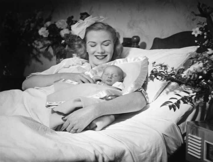 Woman lying on bed, holding new born baby (B&W)