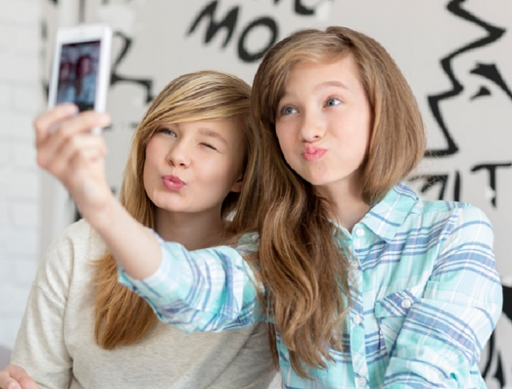 Cute sisters pouting while taking photos with smart phone at home