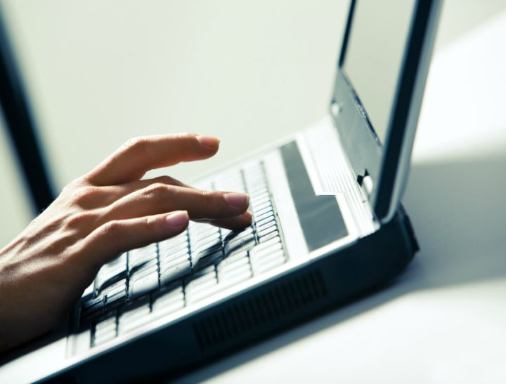 Close-up of businesswomans fingers pushing keys of laptop on desk