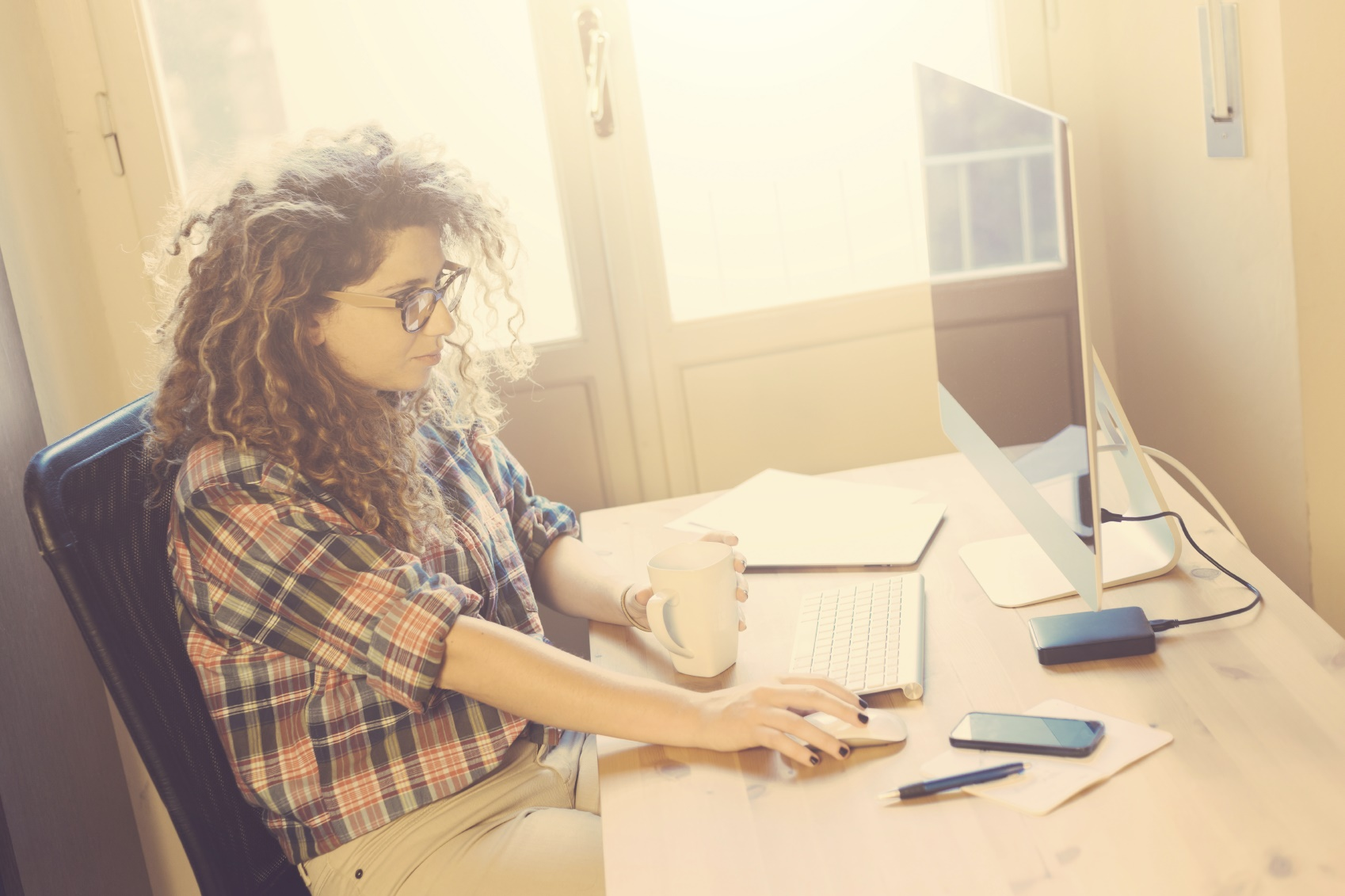 Young woman working at home or in a small office, vintage hipster clothing, curly hair. There is a cup of tea or coffee on the desk with some technological devices.